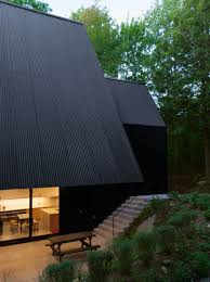 a black contemporary cabin surrounded in the forest home design