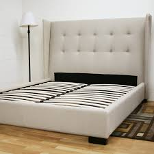 bed on the floor white fabric bed frame with tufted headboard and four black wooden