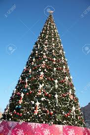 large outdoor tree in snow and ornaments stock photo