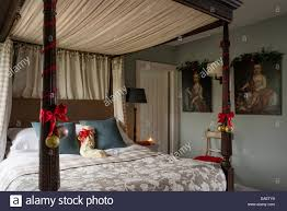 bedroom with four poster bed with red velvet curtains and