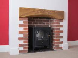 a fireplace with oak beam and sussex red multi stock brick slips