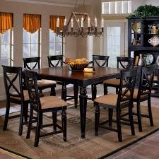 dark wooden mission style dining room chairs under large pendant