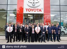 toyota company the staff of a toyota car dealership pose for a group photo