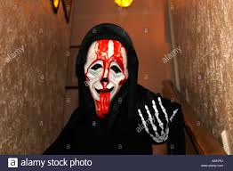 boy dressed up for halloween wearing a scary movie mask stock