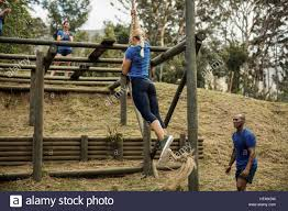 fit woman climbing down the during obstacle course in boot