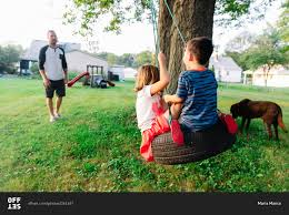dad pushing kids on a tire swing stock photo offset