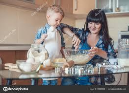 maman baise en cuisine fils tenant coupe mesurage mère fouettant pâte photographie