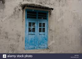 painted blue wooden window shutters on a plain grey concrete wall