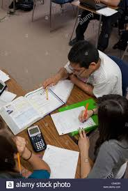 students work together in group using textbook paper and