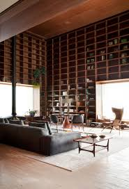 a double height room with floor to ceiling wooden shelves