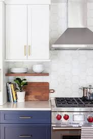 white kitchen cabinets with hexagon backsplash white hexagon backsplash tiles with wolf range