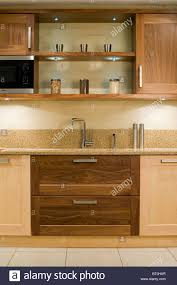 down lit shelves above sink in fitted unit with dark wood drawers