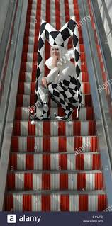 a woman in a harlekin dress is pictured on electric stairs at the