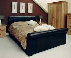 black leather sleigh beds in bedroom with wooden nightstands and