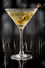 martini green dirty vodka martini served on a dark bar garnished with large