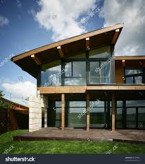 vintage house with brown woden wall large glass window and deck