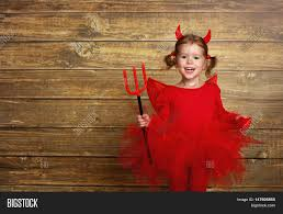 halloween background devil funny child in devil halloween costume with horns and trident