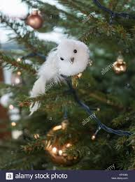 a an white bird decoration on a christmas tree with copper colour