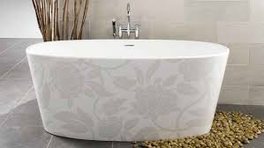 white floral pattern of small bathtub with stainless kohler faucet