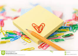small note pad and a pencil with colored paper clips on white
