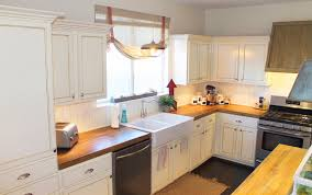 white kitchen island with wooden countertop dark tone cabinets