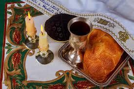 shabbat l shabbat candles in glass candlesticks blurred challah bread stock