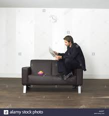 lounge leather ball sofa man suit newspaper reading sit