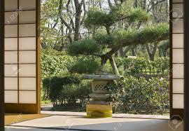 japanese garden seen through a traditional sliding wall of a japanese garden seen through a traditional sliding wall of a wooden house stock photo