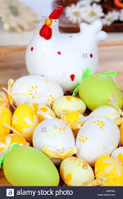 ceramic easter eggs yellow and green easter eggs with a ceramic hen on a wooden floor