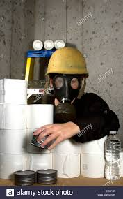 woman dressed in gas mask and hard hat hiding in the basement with