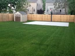 a backyard beautiful green grass surrounds a new basketball court