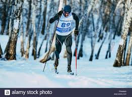 young male skier during race forest in classic style in