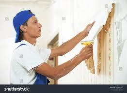 one painter worker peeling off wallpaper stock photo 112396394