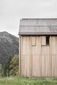 bernardo bader perches larch clad home over concrete plinth in