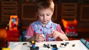 boy play with colored lego pieces at the table of the house stock
