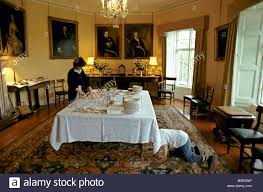 a boy hiding underneath the dinner table in the dining room of a