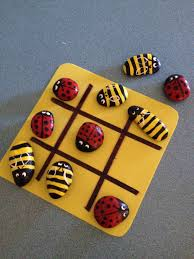 tic tac toe game made from bees and ladybug painted rocks this
