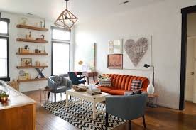 orange and grey sofa with white wooden table on striped rug