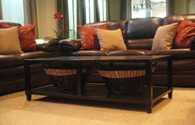 cherry brown leather sofa long brown wooden table with shelf and short legs placed on the