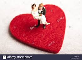 and groom figurines and groom figurines on a heart shape stock photo royalty