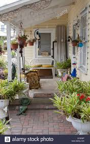 cozy porch of older home with wooden deck and lots of potted