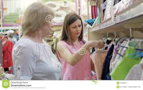 elderly woman clothes elderly woman and woman chooses clothes in the supermarket