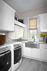 white and gray laundry room with stainless steel apron sink and