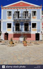 facade painted blue red pink of a three storied neoclassical house