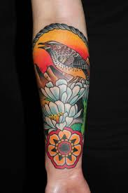 black ink bird in frame with flowers and banner tattoo on left forearm