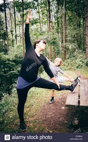 mother and son in forest legs raised on picnic table stretching