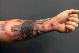 dramatic colored religious themed forearm tattoo of jesus on cross