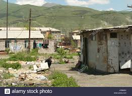 armenia vanadzor man squat amidst debris houses made from shipping