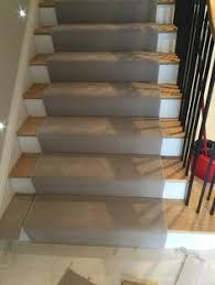 grey carpet to stairs with black whipping stair runners