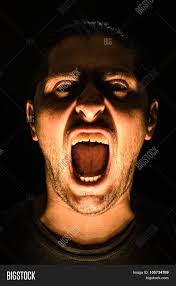 light halloween background horror scene with screaming scary human face with a harsh light on
